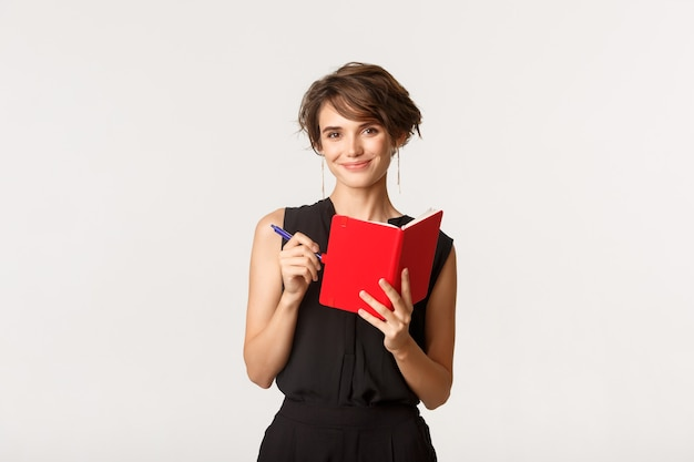 Sorrindo atraente empresário feminino escrevendo sua agenda no planejador, segurando o caderno e a caneta, em pé sobre o branco.