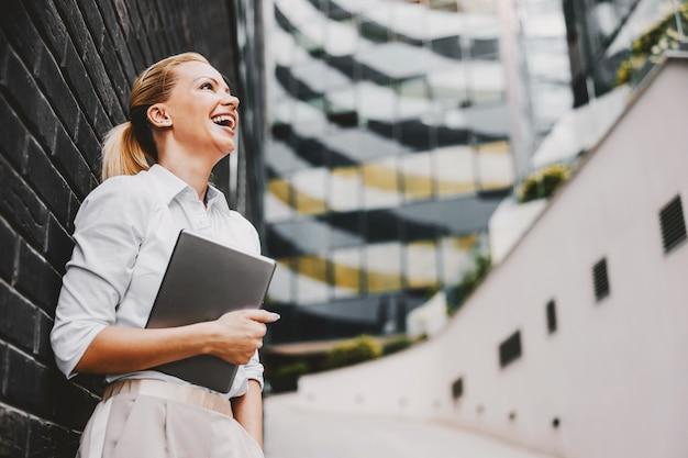 Sorrindo atraente loira elegante empresária em pé ao ar livre e segurando o tablet nos braços. exterior do centro de negócios.
