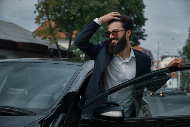 Sorrindo barbudo homem bonito tocando seu cabelo
