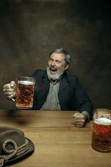 Sorrindo barbudo macho bebendo cerveja no pub