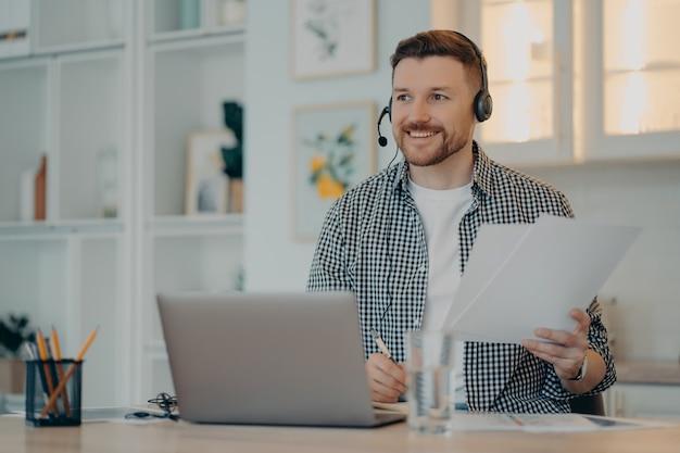 Sorrindo barbudo sentado em seu local de trabalho e segurando documentos durante a reunião online, freelancer masculino trabalhando em casa e usando o laptop, usando fone de ouvido. trabalho remoto e conceito freelance