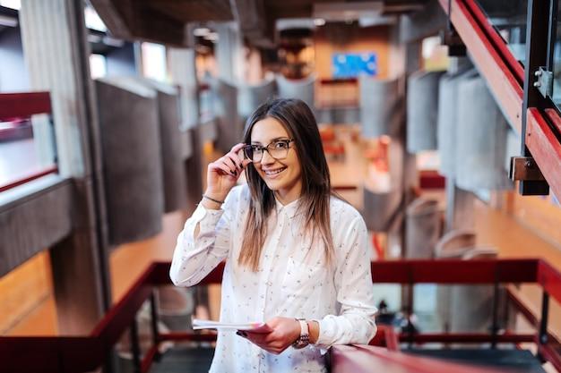 Sorrindo bela aluna com cabelos castanhos e óculos segurando o caderno, em pé e esperando a aula para começar.