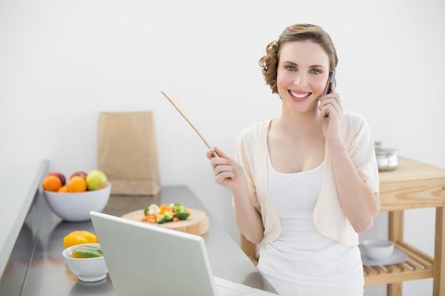 Sorrindo bela mulher telefonando enquanto estava de pé na cozinha na frente de seu laptop