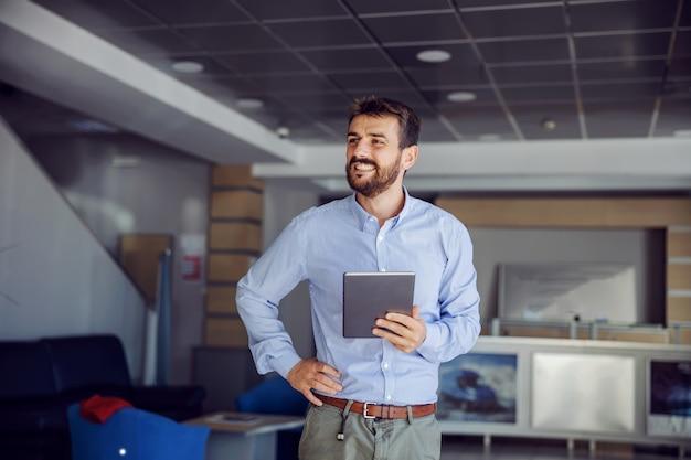 Sorrindo bem sucedido chefe barbudo em pé no saguão da empresa de navegação, segurando o tablet e segurando a mão no quadril. ele está satisfeito porque os negócios vão bem.