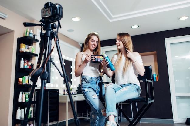 Sorrindo blogueiras de beleza femininas revisando produtos de maquiagem para seu blog, gravando um vídeo na câmera no salão