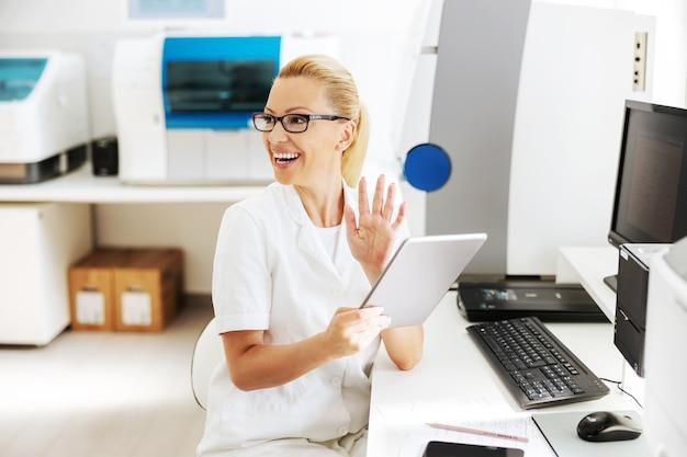 Sorrindo bonito loiro feminino assistente de laboratório em uniforme branco estéril sentado no laboratório e usando o tablet para verificar os resultados da pesquisa.