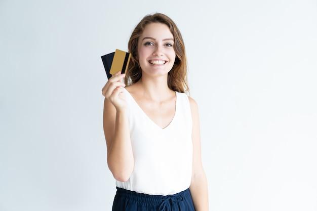 Sorrindo, bonito, mulher jovem, segurando, dois, plástico, cartões