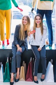 Sorrindo, bonito, mulheres jovens, com, coloridos, bolsas para compras, mostrando, etiqueta venda