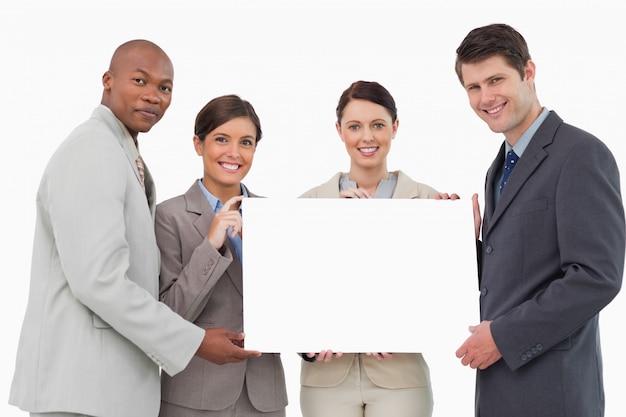 Sorrindo businessteam segurando sinal em branco juntos