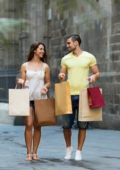 Sorrindo casal amoroso com sacolas de compras na cidade