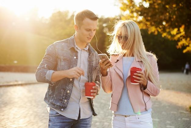 Sorrindo casal apaixonado andando no parque outono, de mãos dadas. ouça música em fones de ouvido e beba café para viagem.