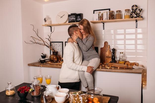 Sorrindo casal apaixonado na cozinha em casa