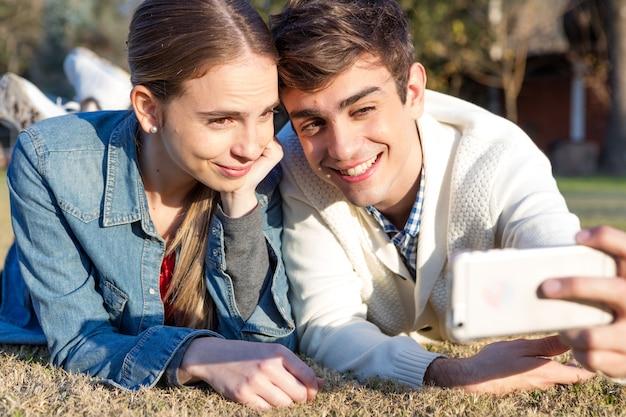 Sorrindo casal de tirar uma foto na grama