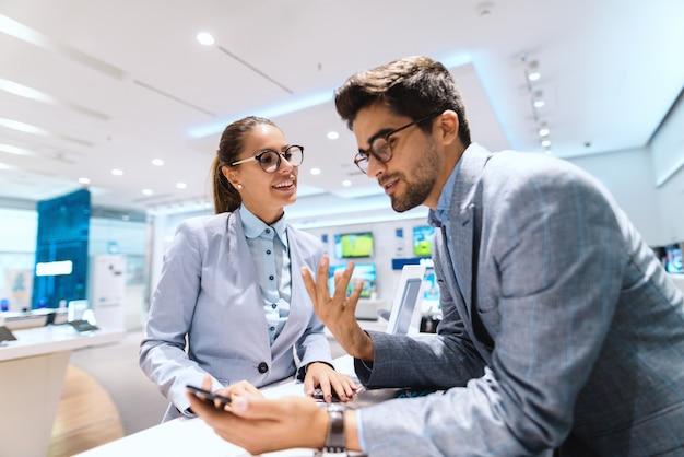 Sorrindo casal multicultural em roupa formal, discutindo sobre o novo telefone inteligente. homem segurando o telefone inteligente e falando enquanto mulher ouvindo ele. interior da loja de tecnologia.