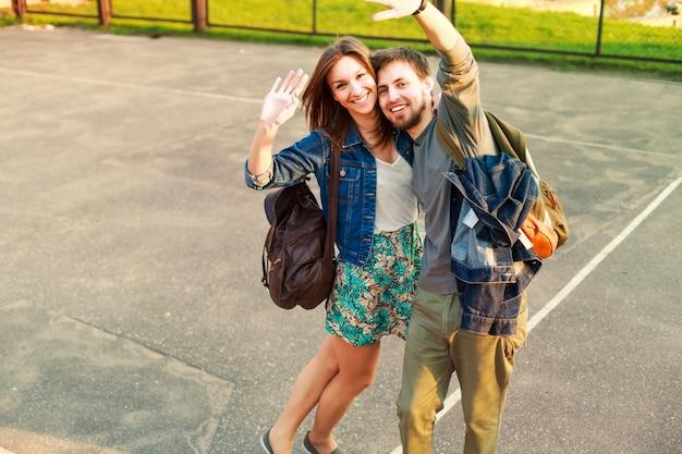 Sorrindo casal posando e dizendo olá