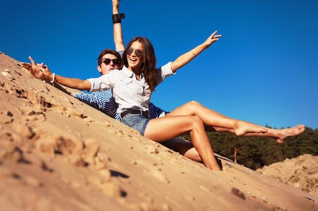Sorrindo casal se divertindo e colocando as mãos no ar na praia