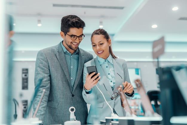 Sorrindo casal vestido elegante escolhendo novo telefone inteligente em pé na loja de tecnologia