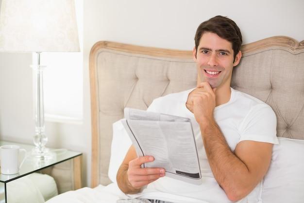 Sorrindo casual homem lendo jornal na cama