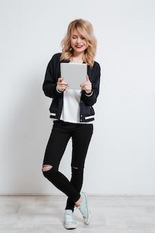 Sorrindo casual jovem adolescente em pé e usando o dispositivo de tablet