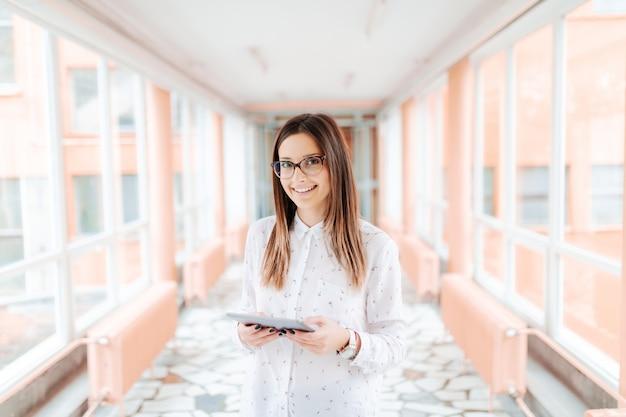 Sorrindo caucasiana professora com óculos usando tablet em pé no corredor.