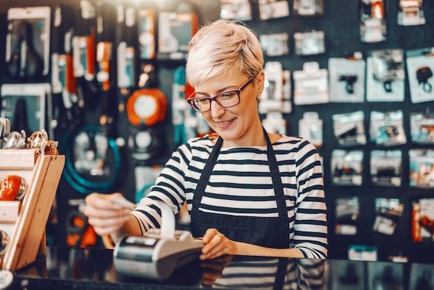 Sorrindo caucasiana trabalhadora com cabelo loiro curto e óculos usando a caixa registradora em pé na loja de bicicletas.