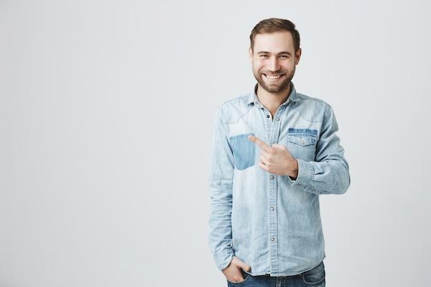 Sorrindo caucasiano homem barbudo, apontando o dedo esquerdo, publicidade