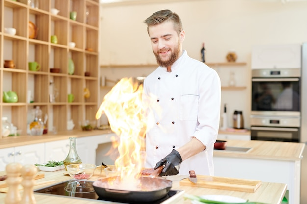 Sorrindo chef de cozinha flambe