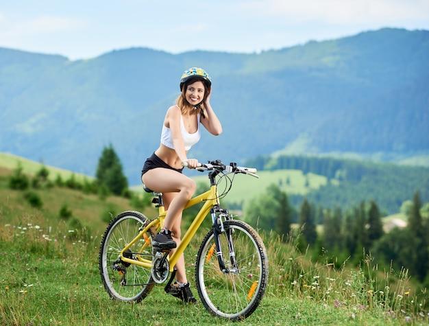 Sorrindo ciclista feminina desportiva na bicicleta amarela em uma trilha rural nas montanhas, usando capacete.