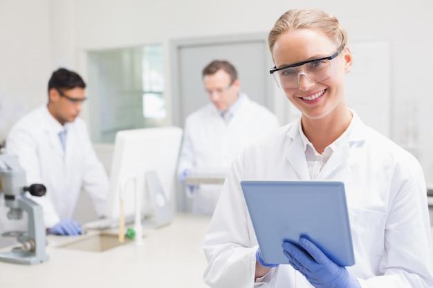 Sorrindo cientista usando tablet enquanto colegas trabalham atrás