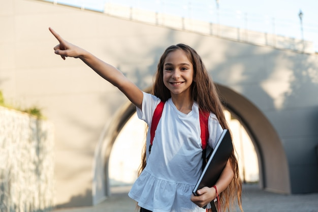 Sorrindo colegial morena posando ao ar livre e apontando para fora