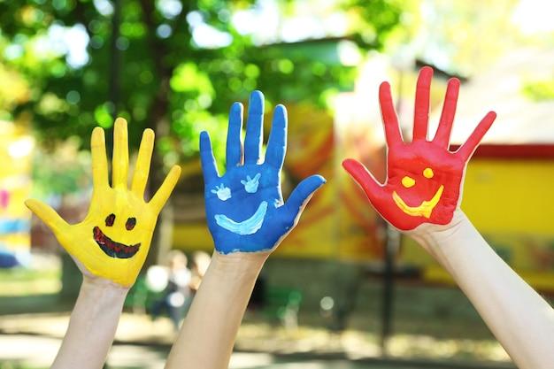 Sorrindo com as mãos coloridas em um fundo natural