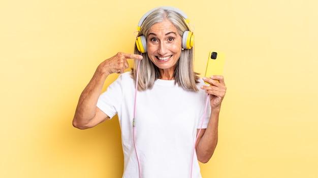 Sorrindo com confiança apontando para o próprio sorriso largo, atitude positiva, relaxada e satisfeita com fones de ouvido