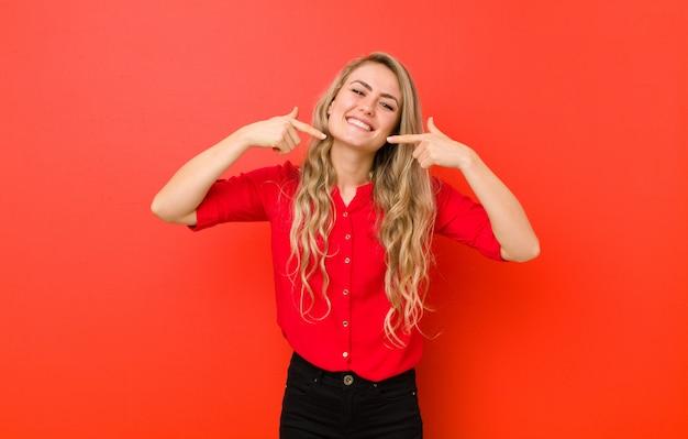 Sorrindo com confiança apontando para o próprio sorriso largo, atitude positiva, relaxada e satisfeita