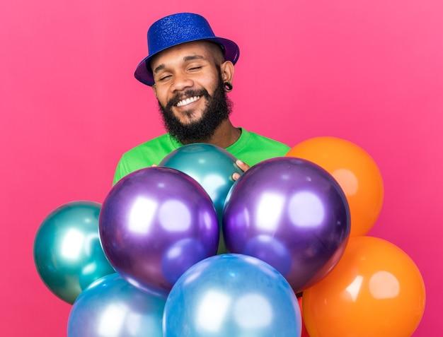 Sorrindo com os olhos fechados, jovem afro-americano usando chapéu de festa atrás de balões isolados na parede rosa