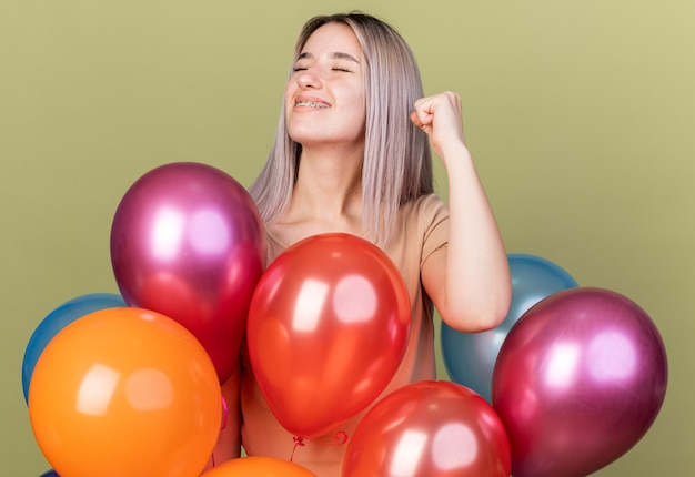 Sorrindo com os olhos fechados, jovem e linda garota usando aparelho dentário em pé atrás de balões, mostrando o gesto de sim, isolado na parede verde oliva