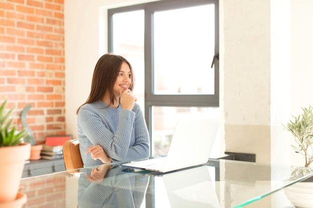Sorrindo com uma expressão feliz e confiante com a mão no queixo, pensando e mulher olhando para o lado