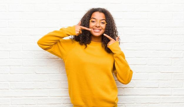 Sorrindo confiante apontando para o próprio sorriso largo, atitude positiva, relaxada e satisfeita
