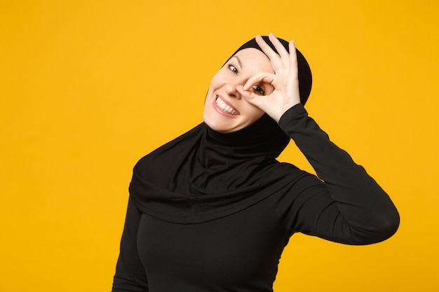 Sorrindo confiante linda jovem muçulmana árabe em roupas pretas de hijab posando isolado na parede amarela, retrato. conceito de estilo de vida do islã religioso de pessoas.