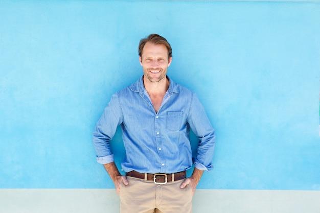 Sorrindo, confiante, posição homem, contra, parede azul