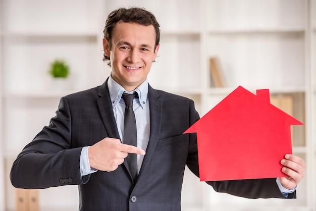 Sorrindo corretor de imóveis homem está segurando um modelo de casa.