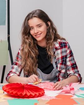 Sorrindo, craftswoman, olhando câmera, enquanto, trabalhando