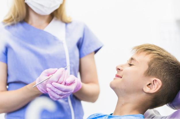 Sorrindo, criança, paciente, frente, femininas, odontólogo, segurando, scaler