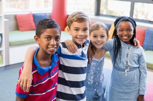 Sorrindo crianças da escola em pé com o braço na biblioteca