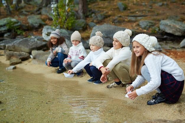 Sorrindo crianças sentadas pela água