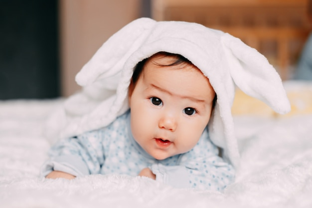 Sorrindo, cute, bebê criança, em, traje coelho, mentindo, ligado, pele