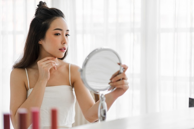 Sorrindo da jovem mulher asiática bonita limpa fresca saudável pele branca olhando mirror.girl tocando em seu rosto com a mão e aplicar o creme em casa. conceito de spa e beleza