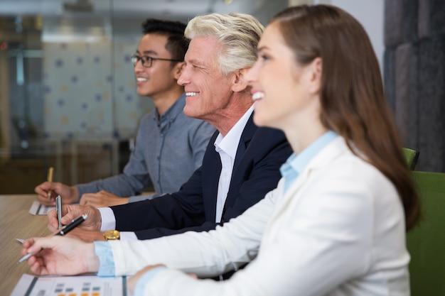 Sorrindo de negócios sênior sentado na conferência