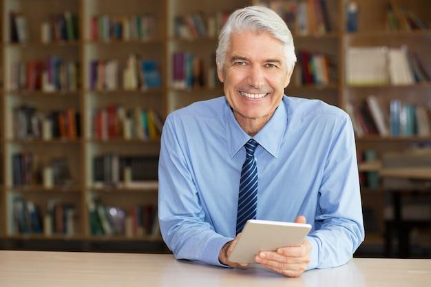Sorrindo de negócios sênior usa a tabuleta digital