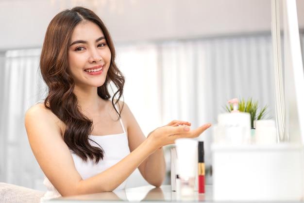 Sorrindo de uma jovem linda mulher asiática limpa, fresca, saudável, pele branca, olhando para a garota camara.asian segurando a loção corporal e aplicando creme hidratante