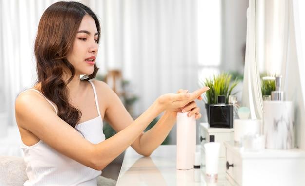 Sorrindo de uma jovem linda mulher asiática limpa pele branca saudável fresca olhando para o espelho. menina asiática segurando loção corporal e aplicando creme hidratante em casa